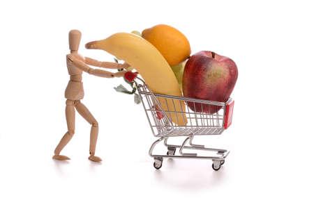 marioneta de madera: Marioneta de madera pequeña con un carrito de la compra lleno de frutos sanos