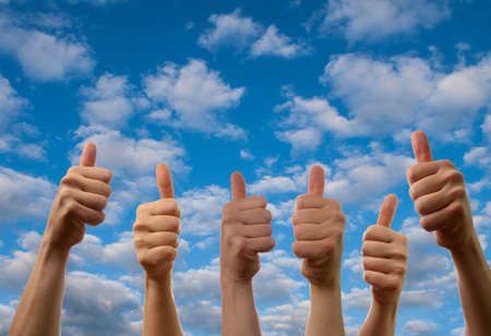 Six hands with thumbs up on a summer sky background