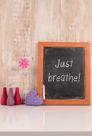 chalkboard with the words Just breathe, wellness and health care concept photo