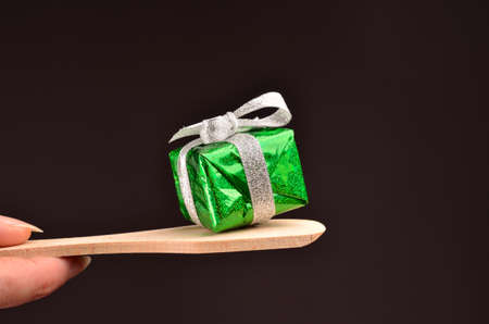 golden shovel: Green Christmas gift box with a bow on a dark background Stock Photo