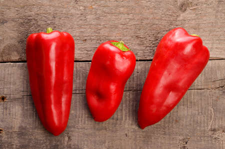 old red barn: Three red fresh paprika on an old used barn wood Stock Photo