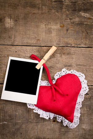 old photograph: Old photograph with a red fabric heart shape on an used rustic table