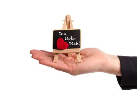 als: Hand hält Staffelei mit einer kleinen Tafel, Ich liebe Dich! als Valentinsgruß