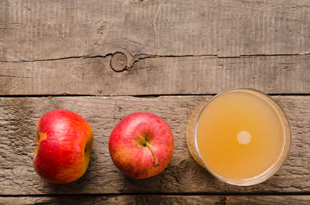 non alcoholic beverage: Fresh apples with organic apple juice on a rustic wooden table, top view