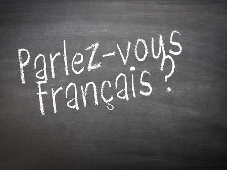 francais: Learning French language concept of teacher or student writing parlez-vous francais (do you speak French) on blackboard  chalkboard.
