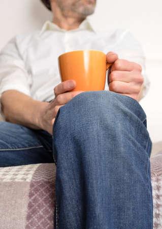 having a break: Man on a sofa having a break with a pot of coffee