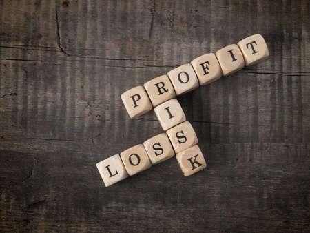 perdidas y ganancias: palabras cruzadas con las palabras beneficios, la p�rdida y el riesgo de madera dados Foto de archivo