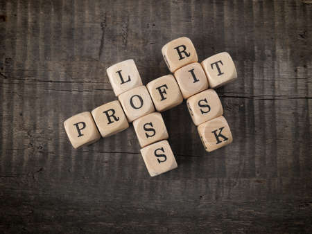 perdidas y ganancias: Cross words with the words profit, loss and risk on wooden dices