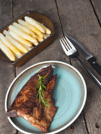 rips: Grilled rips with white asparagus on a wooden table