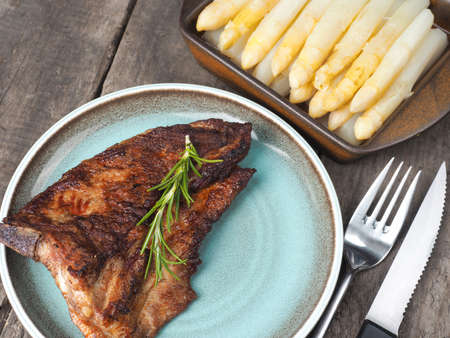 rips: Spicy grilled rips with white asparagus on a rustic wooden table Stock Photo