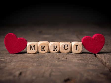 Kleine houten dobbelstenen met het Franse woord van Dank u met twee rode hartvormen op hout Stockfoto