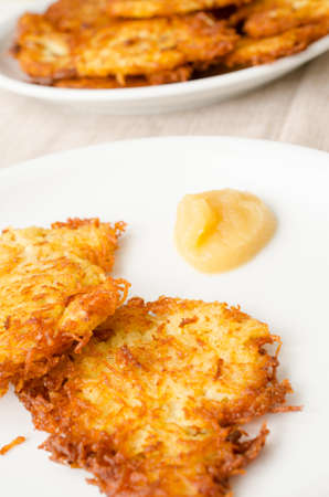 fritters: Potato fritters and applesauce on a white plate in a restaurant Stock Photo