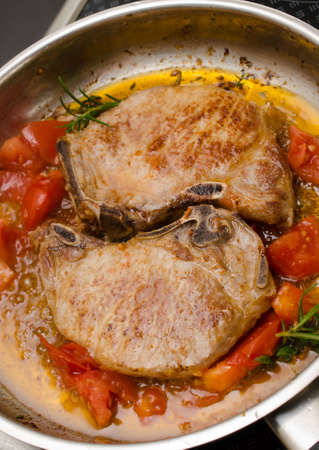 steel pan: Pork chop with herbs and tomatoes in a steel pan