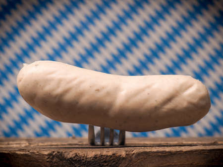 veal sausage: Bavarian veal sausage on a fork in front of a Bavarian flag, selective focus on the sausage Stock Photo