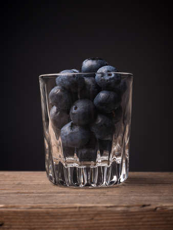super food: Blueberries in a glass on a wooden table, super food concept image
