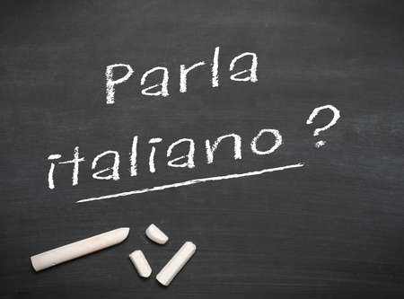 Learning Italian language concept of teacher or student writing parla italiano (do you speak Italian) on blackboard  chalkboard.