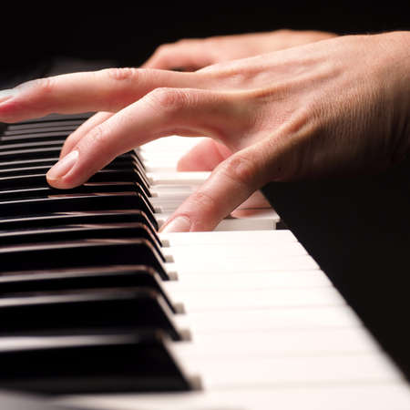 Close up shot of male hands playing piano with selective focus