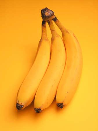 Three fresh bananas on a yellow background