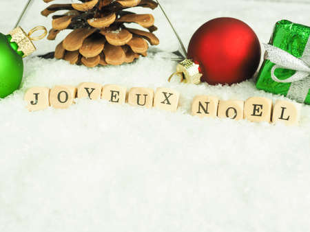 Christmas decoration in snow with the French words Merry Christmas on wooden dices