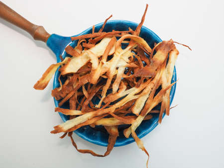 Homemade parsnip chips in a rustic blue ceramic bowl on a white table