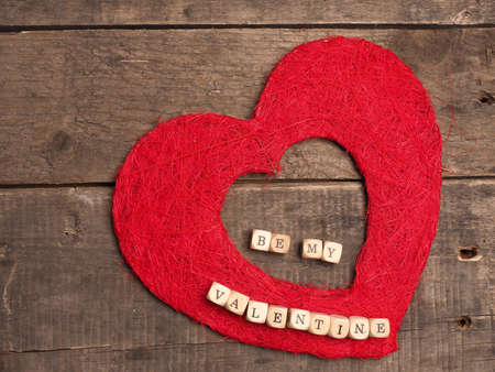 Love concept background, with red heart shape on rustic wood with the words, be my valentine