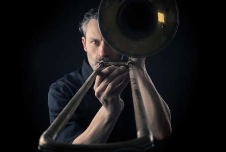 trombon: Portrait of a musician with an old dusty trombone on a dark background