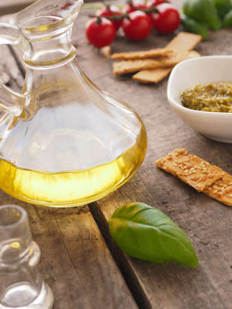 Pesto verde with olive oil and fresh ingredients on a rustic wooden background