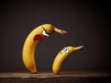 Big angry banana boss with small employee Stock Photo