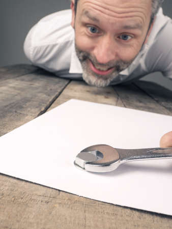 concluding: Crazy business man with a wrench concluding a contract Stock Photo