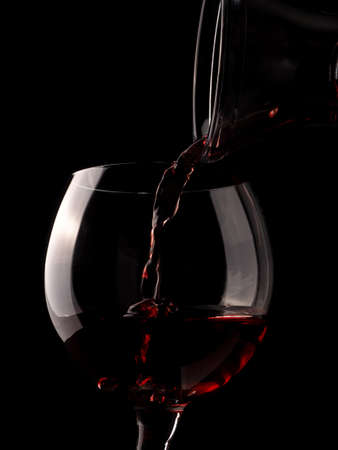 Glass of red wine with an old rustic decanter on a dark background Stock Photo
