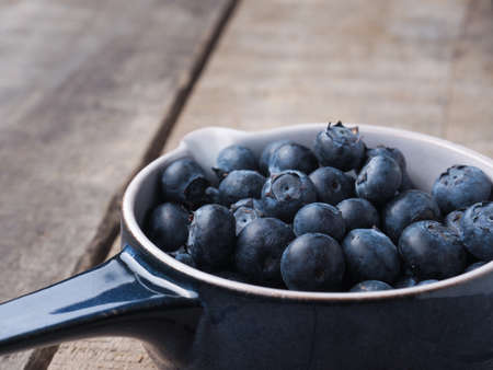 Fresh organic blueberries in a rustic blue bowl on old wooden plank Stock Photo