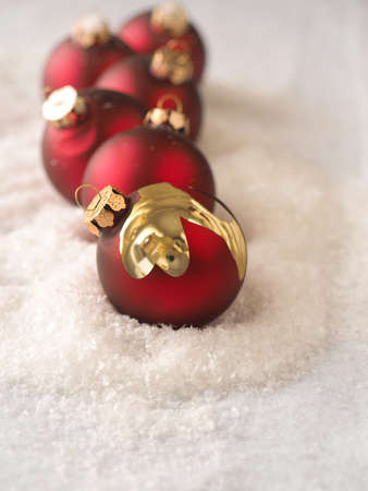 Old red vintage Christmas baubles in a row on snow, Christmas card background Stock Photo