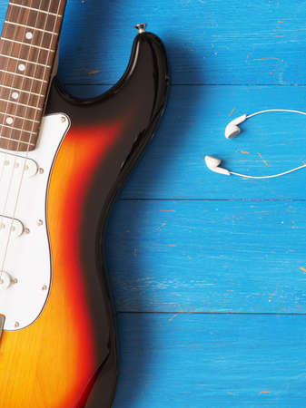 Music concept image, vintage guitar with earphones on a rustic wooden background, Jazz, rock or blues music concept Stock Photo