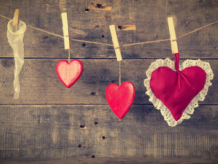 Valentines Day card with red heart shapes and a condome on a wooden wall