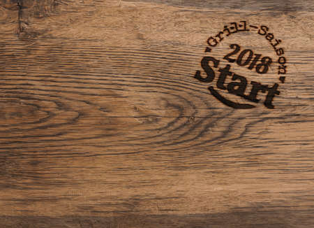 Old used oak plank using a background, wooden texture with the German words Grill season 2018 as a stamp Stok Fotoğraf