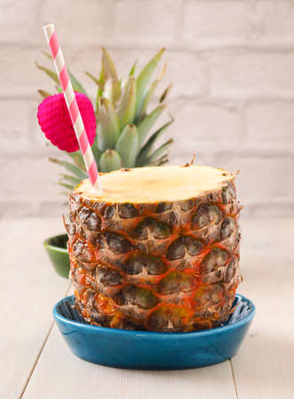 Fresh organic pineapple with a drinking straw on a wooden table