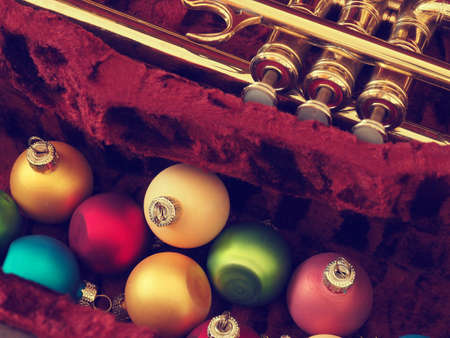 Colorful vintage Christmas baulbes with an old used trumpet, Christmas music background