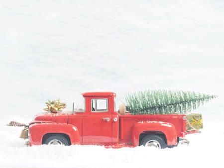 Red vintage pickup truck with a Christmas tree in winter landscape Stock Photo
