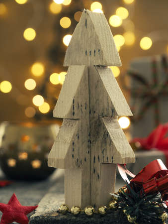 Wooden Christmas tree with decoration and blurred lights in the back