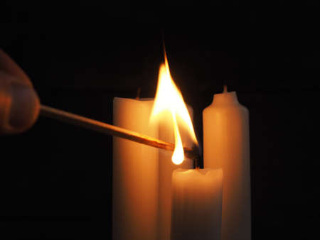 Close up of a hand light a candle on a dark background
