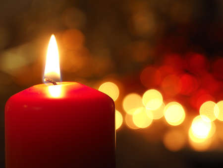 First Advent candle burning with Christmas decoration on a wooden table