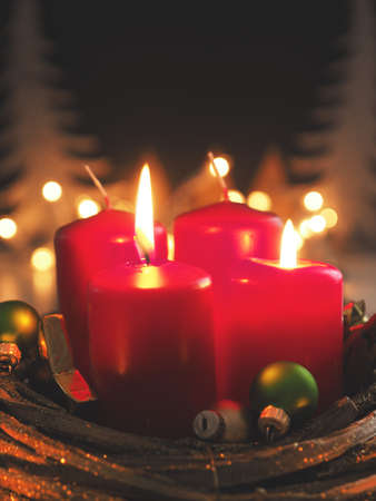 Red Advent candles with decoration in a dark room, space for text or image