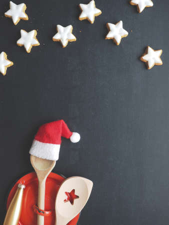 Wooden cooking spoon with hat of Santa on a blank chalkboard, Christmas menu or cooking concept