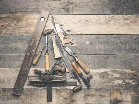 Outils de menuisier vintage comme arbre de Noël sur une vieille table en bois rustique avec un espace pour le texte sur la droite