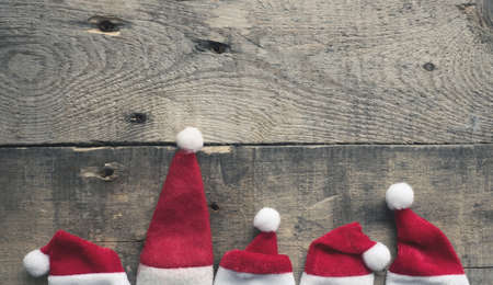 Santa Claus is coming, five hat of Santa on a rustic wooden background with space for text