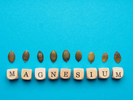 Organic pumpkin seeds with the word magnesium on small wooden dices, healthy food concept with space for your text or image
