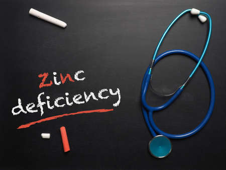 Blackboard with the words zinc deficiency and a stethoscope, medical or health care concept 写真素材