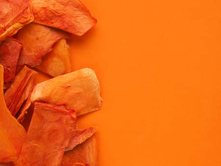 Dried organic papaya slices on an orange studio background, healthy food concept, view from above, space for text