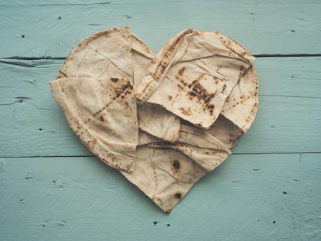 Heart shaped flatbread on a rustic wooden kitchen table, view from above