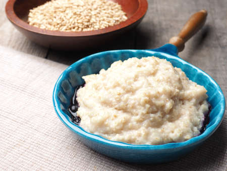 Tasty organic porridge in a blue ceramic bowl on a rustic wooden kitchen table